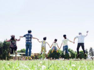 青空に向かってジャンプする家族